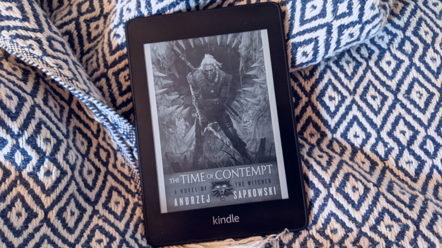 Kindle Paperwhite E-reader displaying cover for Time of Contempt by Andrej Sapkowski and sitting on ikat pattern blanket