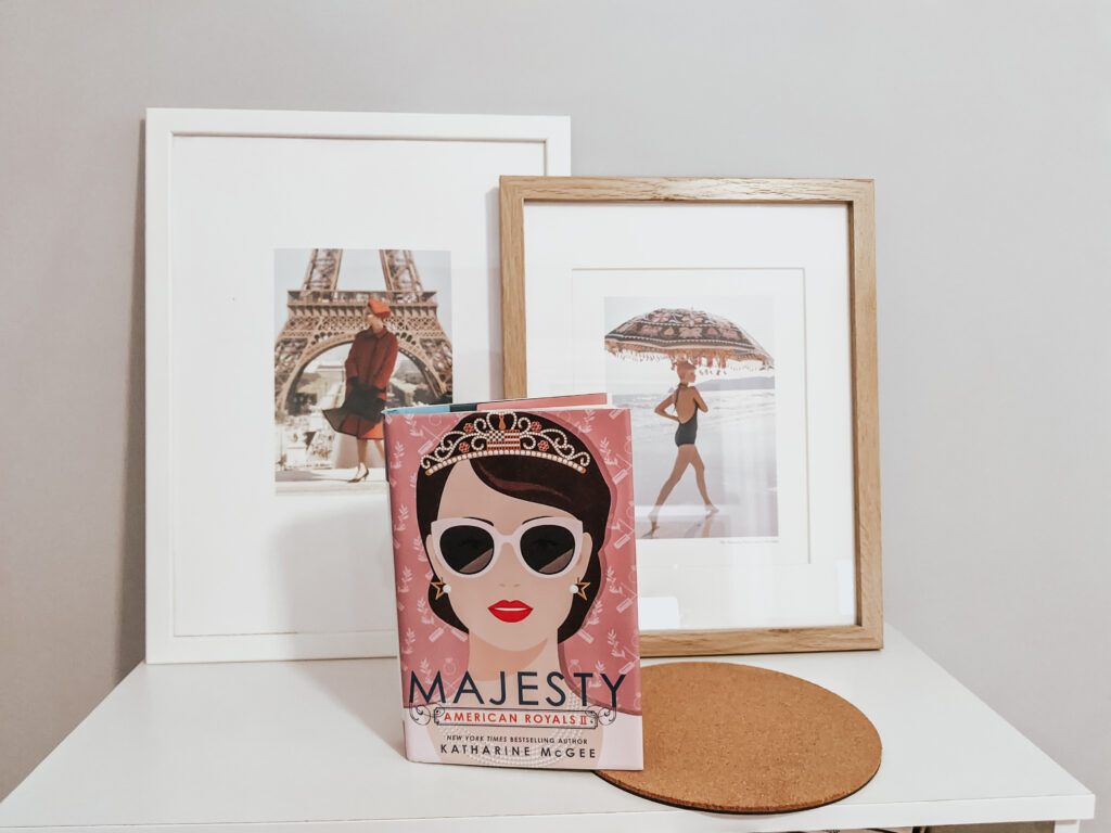 Book Majesty by Katherine McGee propped up on a bookshelf with two photos of women in frames in the background