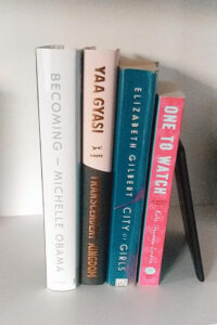 Tall Stack of books containaing Becoming by Michelle Obama, One to Watch by Kate Stayman-London, City of Girls by Elizabeth Gilbert, Transcendent Kingdom by Yaa Gyasi, and an Amazon Nook e-reader