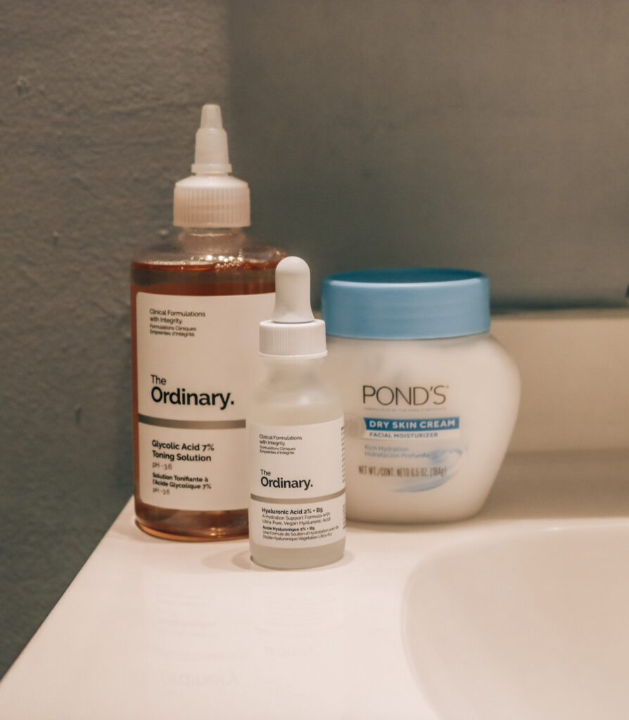 Cluster of skincare products: The Ordinary's Glycolic Acid 7% Toning Solution, The Ordinary Hylauronic Acid 2% with B5, and Pond's Dry Skin Cream