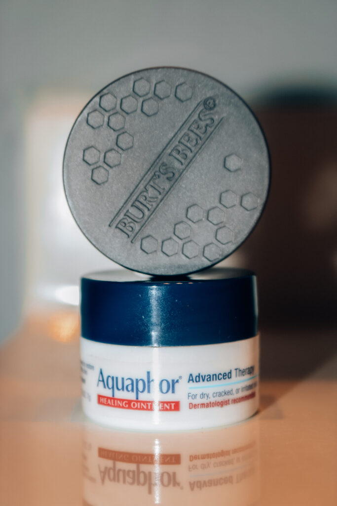 Stack of skincare products: Aquaphor Advanced Therapy Healing Ointment for lips and Burt's Bees Overnight Intensive Lip Treatment.
