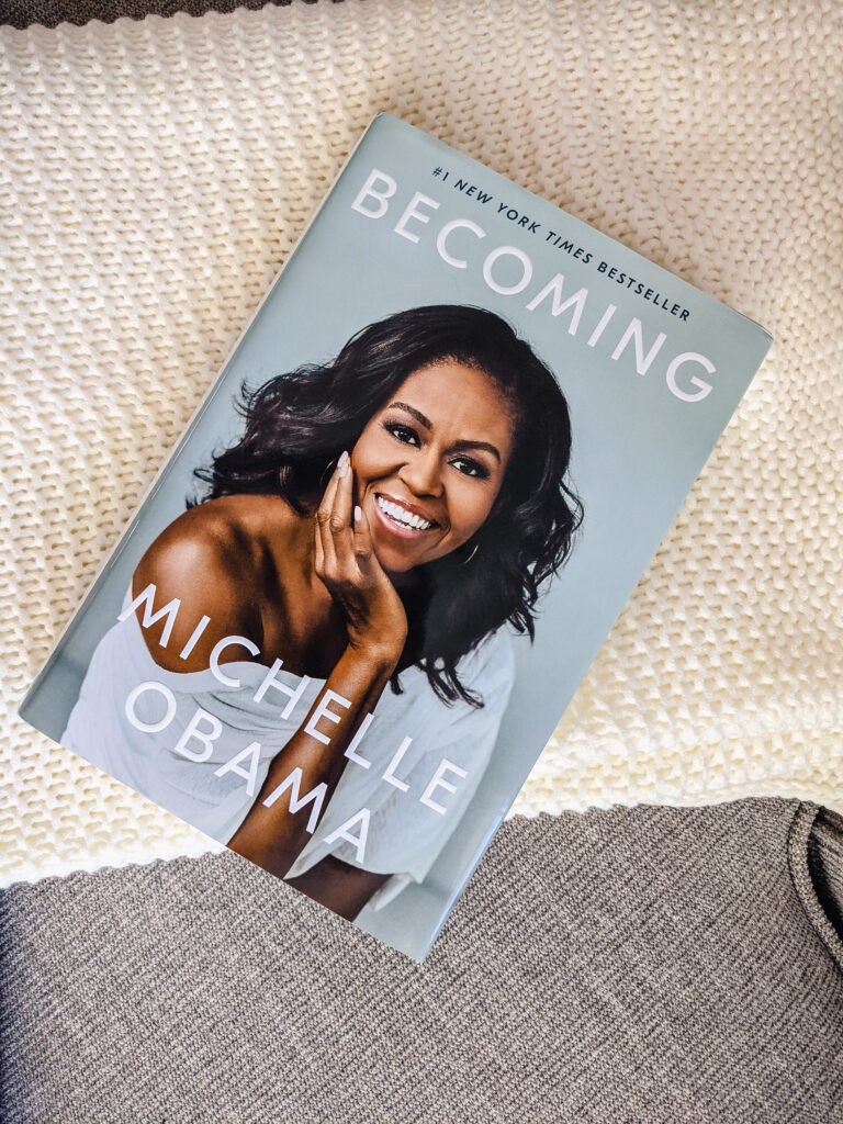 The book I read this month, Becoming by Michelle Obama, placed on a tan fabric couch and white knit blanket.