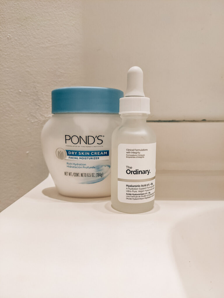 Two budget-friendly summer skincare products in my nighttime skincare routine: short squat white and blue jar of Pond's Dry Skin Cream, and The Ordinary Hyaluronic Acid.