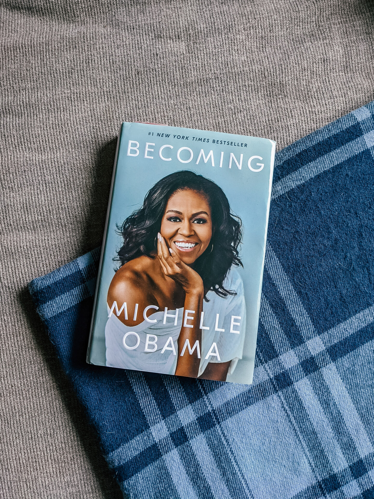 The book I read this month, Becoming by Michelle Obama, placed on a tan fabric couch and blue plaid blanket.