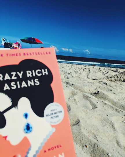 2020 summer reading bookCrazy Rich Asians by Kevin Kwan posed on a LBI Region beach